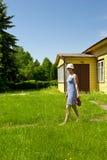 Jarro que lleva de la mujer joven por la casa de verano Foto de archivo