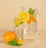 Jarro, vidrio con la bebida, anaranjado maduro y menta imagen de archivo libre de regalías