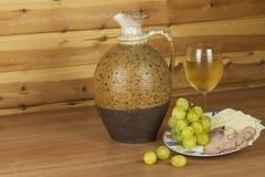 Jarro viejo de la arcilla y un vidrio de vino en una tabla de madera Vino blanco y bocados Jamón, queso y uvas a comer Foto de archivo libre de regalías