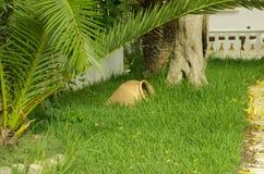 Jarro viejo grande de la loza de barro en hierba verde foto de archivo libre de regalías