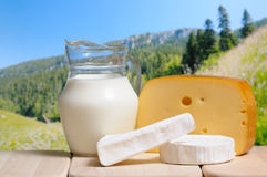 Jarro y queso de leche contra montañas Imagen de archivo