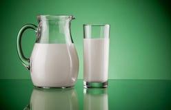 Jarro y vidrio con leche Fotos de archivo