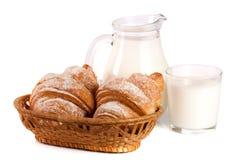 Jarro y vidrio de leche con el cruasán aislado en el fondo blanco Imagenes de archivo