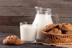 Jarro y vidrio de leche con las galletas de harina de avena en una cesta de mimbre en un fondo de madera Imagen de archivo