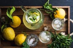 Jarro y vidrios con limonada hecha en casa, cubos de hielo en la bandeja de madera, visión superior Foto de archivo