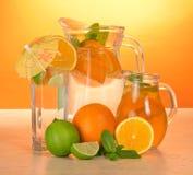 Jarros con las bebidas, el vidrio, la cal jugosa y las naranjas Fotografía de archivo