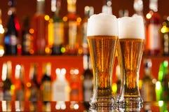Jarros de cerveja servidos no contador da barra imagem de stock