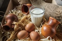 Jarros de la arcilla, huevos, vidrio de leche, en la paja y una arpillera Fotos de archivo