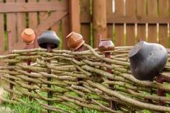 Jarros velhos em uma cerca de madeira Os elementos decorativos da paisagem projetam sob a antiguidade Fotografia de Stock Royalty Free