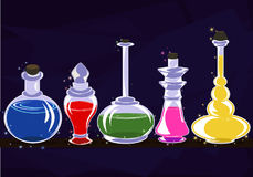 Jars of the Alchemist with magic potions on the shelf. Banks of various shapes with multi-colored liquids stand in a row on the shelf Royalty Free Stock Images