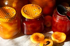 Jars with apricot and plum jam on a wooden background. Bright Sunlight stock photo