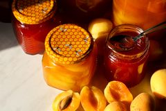 Jars with apricot and plum jam on a wooden background. Bright Sunlight royalty free stock photography