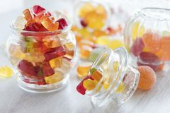 Jars of backlit colorful gummy candies stock photo