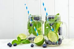 Jars of blueberry, lime, mint, detox water over white wood Stock Photos