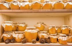 Jars of candied lime honey on the shelf in shop. Sale of natural honey in market. Production of honey.  stock photos