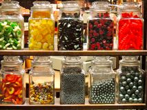 Jars in a candy store. Racks of jars seen through the shop window of a candy store with silver bearings, cough candies, dolly mixture, sours, and red and black Stock Photography