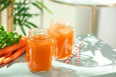 Jars of carrot juice. On table royalty free stock photography