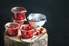 Jars with cherry compote on a wooden tree trunk Royalty Free Stock Photography
