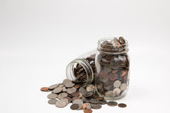 Jars of coins. Containers of coins with a jar tipped over spilling Royalty Free Stock Photos