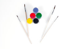 Jars with colored gouache and brush for drawing on a white background laid out in the shape of a flower. Stock Images