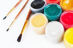 Jars with colored gouache and paint brushes. Royalty Free Stock Photography