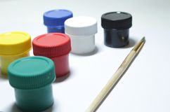 Jars with gouache and paint brushes on a white background royalty free stock photography