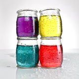Jars of colored water stacked Royalty Free Stock Photography