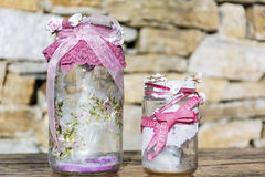 Jars decorated with roses and lace on a stone background .Home decoration Royalty Free Stock Image