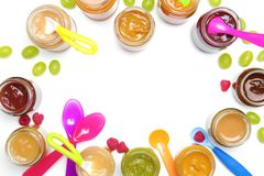 Jars with different baby food and spoons. On white background royalty free stock image