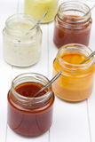 Jars filled with barbecue sauces Royalty Free Stock Image