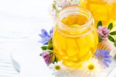 Jars with fresh flower honey on white wooden board, top view. Jars with fresh flower honey on white wooden board, closeup stock photography