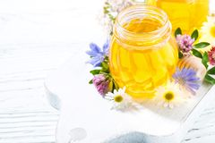 Jars with fresh flower honey on white wooden board, top view. Horizontal royalty free stock photography