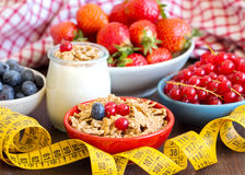 Jars of fresh yogurt, berries, muesli and measuring tape Stock Photos