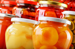 Jars with fruity compotes jams and pickled vegetables Stock Image