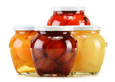 Jars with fruity compotes on white. Preserved fruits Stock Image