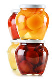 Jars with fruity compotes on white. Preserved fruits Royalty Free Stock Photography