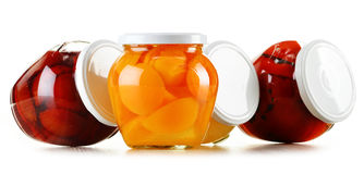 Jars with fruity compotes on white. Preserved fruits Stock Images