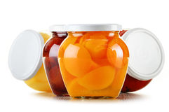 Jars with fruity compotes on white. Preserved fruits Stock Photos