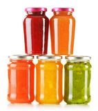Jars of fruity jams on white background Royalty Free Stock Photos