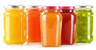 Jars of fruity jams on white background. Preserved fruits Royalty Free Stock Photo