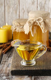 Jars and glass jug of honey on wooden table Stock Image