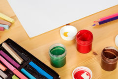 Jars of gouache stand on the wooden table next to a box of crayo Stock Image
