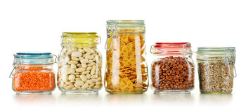Jars with grain foods on white Stock Photography