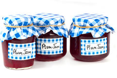 Jars of home-made plum jam. Home made plum jam  in glass jars with checked blue paper cover and hand written labels. on white Stock Photos