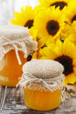 Jars of honey and beautiful sunflowers Royalty Free Stock Images