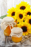 Jars of honey and beautiful sunflowers Stock Images