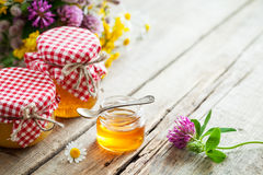 Jars of honey and healing herbs bunch on table Stock Photo