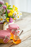 Jars of honey and healing herbs bunch on table. Royalty Free Stock Images