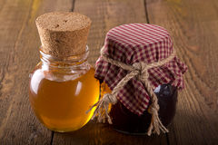Jars of honey and jam, rustic. Jars of honey and jam on a rustic table Royalty Free Stock Images