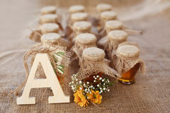 Jars with honey and orange flowers on a sacking background. Stock Photography